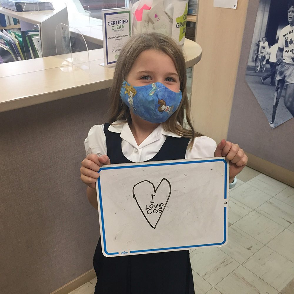 student holding an I Love CGS sign.